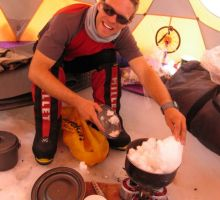 Paul melting snow inside the cook tent at camp 1