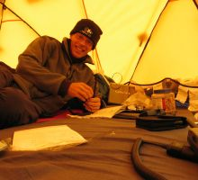 Paul relaxing in his tent and writing a blog post at Everest basecamp