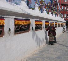 A nepalese woman spinning the prayer wheels in Kathmandu