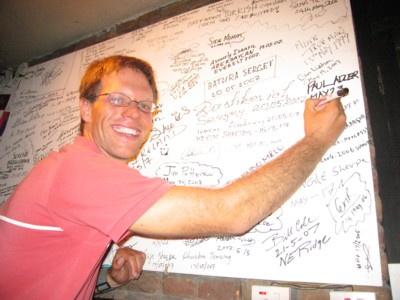 Paul signs his name on the famous Rumdoodle wall.