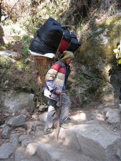 Porter carrying a heavy load up to Namche Bazaar. Photo Paul Adler.